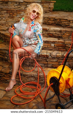 Beautiful woman having fun with garden hose splashing summer rain. - stock photo