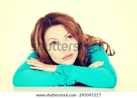 Beautiful woman having her head on hands. Looking up. - stock photo