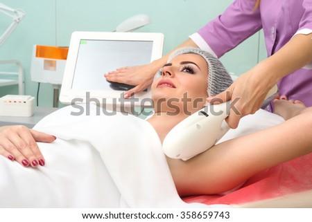 Beautiful woman having underarm Laser hair removal epilation. Laser treatment in cosmetic salon - stock photo