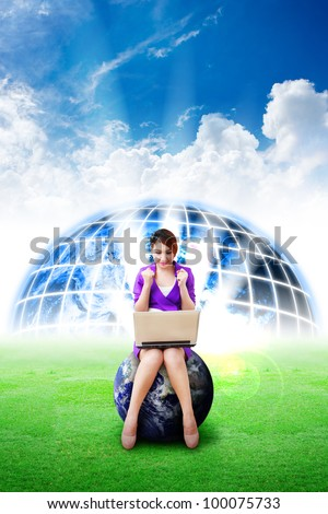 Beautiful woman hold notebook computer and digital world background on the grass field : Elements of this image furnished by NASA - stock photo