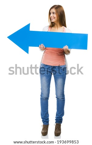 Beautiful woman holding a blue arrow pointing to her left side - stock photo