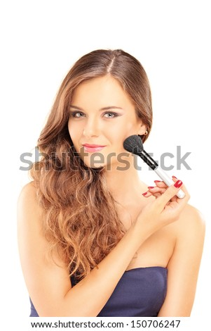 Beautiful woman holding a brush and applying make-up isolated on white background - stock photo