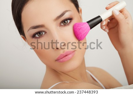 beautiful woman holding a powder brush near her face, studio white - stock photo
