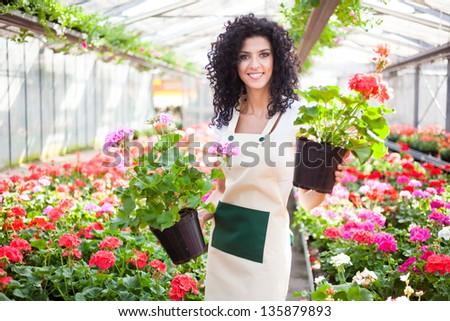 Beautiful woman holding flower pots - stock photo