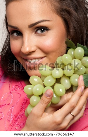 Beautiful woman holding green grape in her hands - stock photo