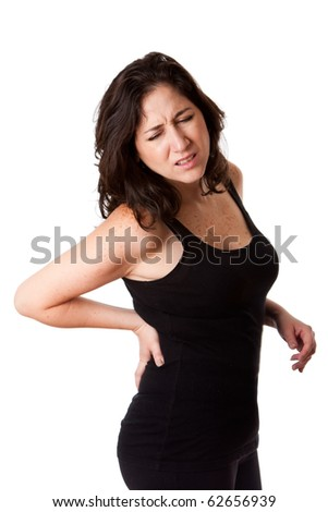 Beautiful woman holding her back with pain and ache due to injury,wearing a sporty black tank top, isolated. - stock photo