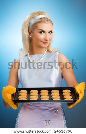 Beautiful woman holding hot roasting pan with oat cookies on it. Retro stylized portrait - stock photo