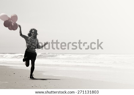beautiful woman holding red balloons and walking on seaside - stock photo