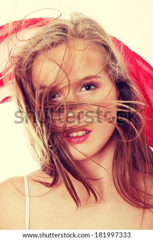 Beautiful woman holding red color scarf on white (posing with wind) - stock photo