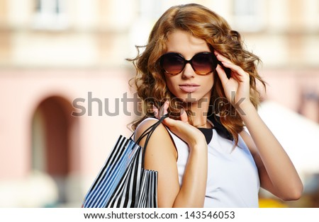 Beautiful woman holding shopping bags and smiling - outdoors - stock photo