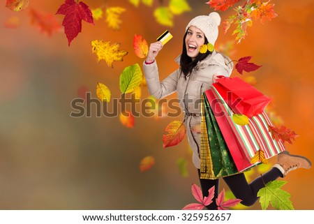 Beautiful woman holding shopping bags, buying in autumn season. Happy female shopper. - stock photo