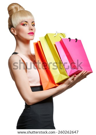 Beautiful woman holding shopping bags isolated on white background. Confident blonde girl boasting purchases. Pinup hairstyle, fringe, pink bow. Happy fashionable shopaholic. Glamorous bright makeup - stock photo