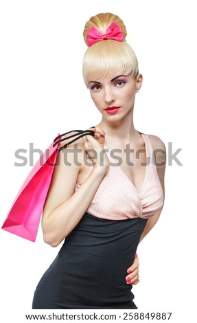 Beautiful woman holding shopping pink bag isolated on white background. Confident blonde girl boasting purchase. Pinup hairstyle, fringe and pink bow. Happy fashionable shopaholic. Glamorous makeup - stock photo