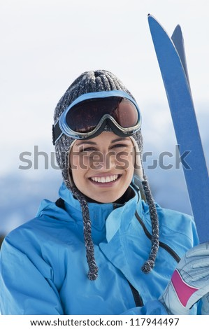 Beautiful woman holding skis and looking at camera - stock photo