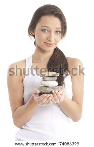 Beautiful woman holding spa stones - stock photo