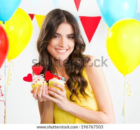 Beautiful woman holding two cupcakes - stock photo