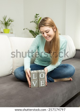 Beautiful woman holding wooden bricks with letters making word Love - stock photo