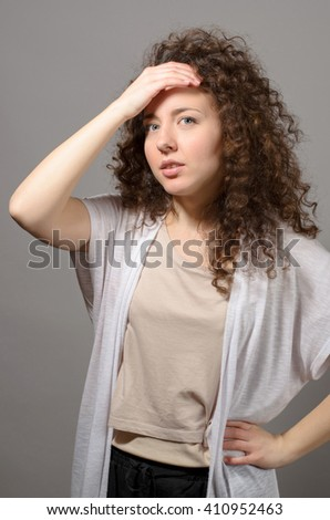 Beautiful woman holds a head on grey background - stock photo