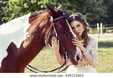 Beautiful woman hugging a horse - stock photo