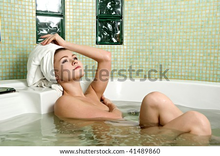 beautiful woman in a bathroom with a towel on a head - stock photo