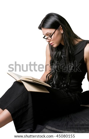 Beautiful woman in a black dress reading a book - stock photo