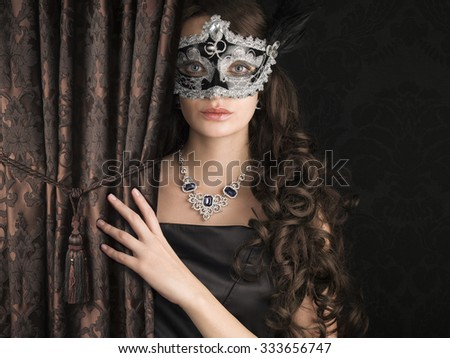 Beautiful woman  in a carnival mask behind the satin embroidered curtain with lace pattern on dark background.  - stock photo