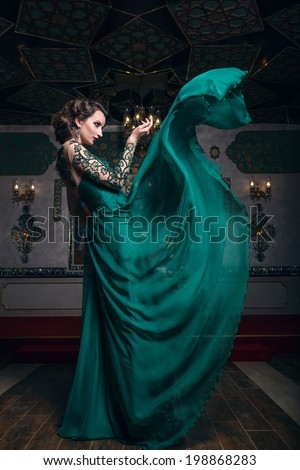 Beautiful woman in a green long dress on a background of richly decorated room. Fashion woman in fluttering dress. - stock photo