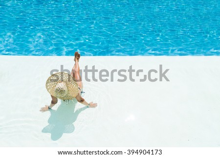 beautiful woman in a hat sitting on the edge of the swimming pool - stock photo