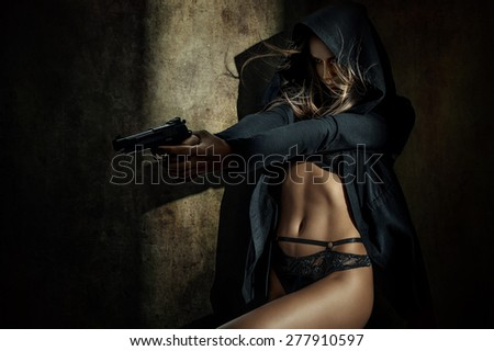 Beautiful woman in a luxurious lingerie and hood with a gun - stock photo