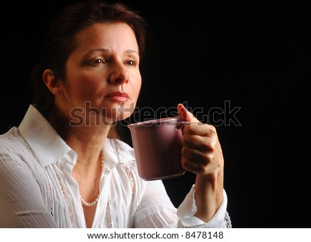 Beautiful woman in a melancholy mood over a cup of coffee - stock photo