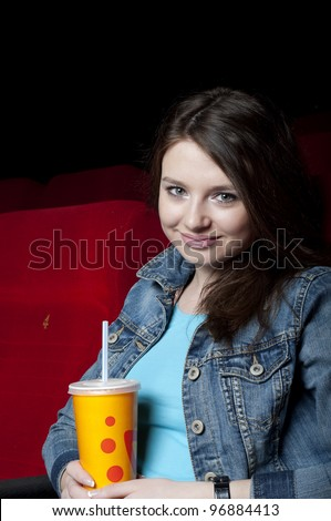 beautiful woman in a movie theater, watching a movie and drink a drink - stock photo