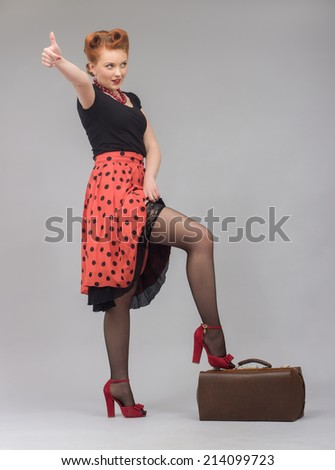 Beautiful woman in a pin-up with a traveling bag catches the car with his hand raised. - stock photo