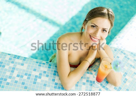 Beautiful woman in a pool with a cocktail next to her - stock photo