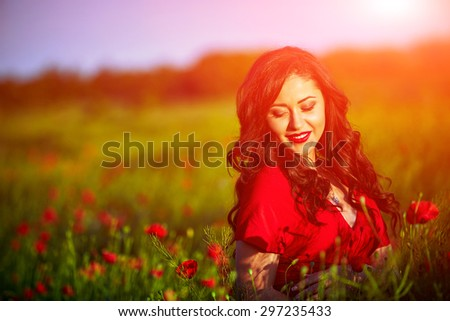 Beautiful woman in a poppy field with flowers. Woman wearing in a red dress. - stock photo