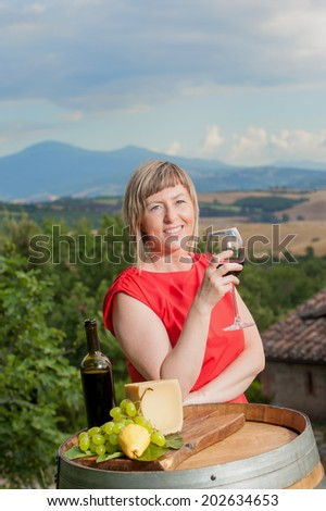 Beautiful woman in a red dress tasting red wine in the hills of Tuscany, Italy - stock photo