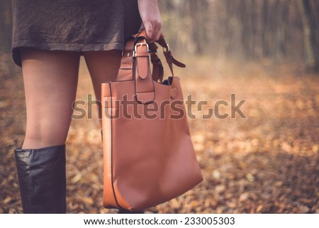 Beautiful woman in a romantic autumn fall scenery holding brown leather handbag. Fashion woman ready for shopping - stock photo