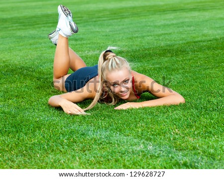 Beautiful woman in a sports suit lying on a green soccer field at the stadium - stock photo