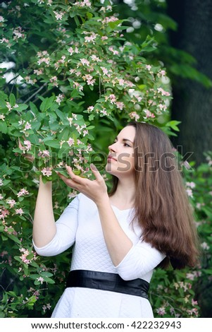 Beautiful woman in a spring garden with blooming honeysuckle - stock photo