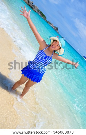 Beautiful woman in a swimsuit striped blue hat standing with arms outstretched to life carefree at sea and sky in summer on the beach of Miang Island, Mu Ko Similan National Park, Phang Nga, Thailand - stock photo