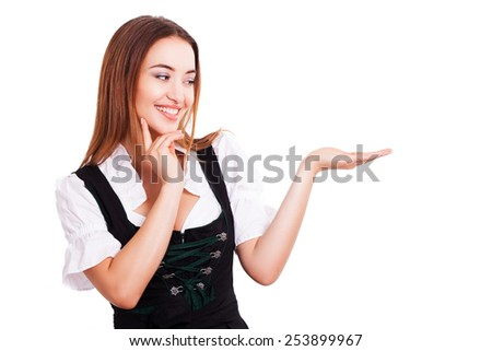 beautiful woman in a traditional bavarian dirndl with an offer - stock photo