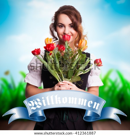 beautiful woman in a traditional bavarian dirndl with flowers - stock photo