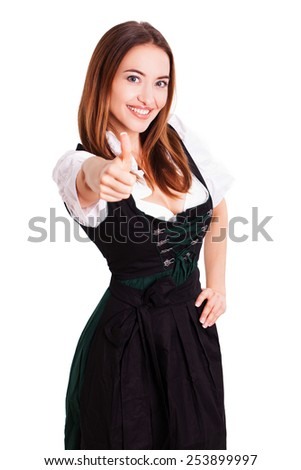 beautiful woman in a  traditional bavarian dirndl with thumb up gesture - stock photo