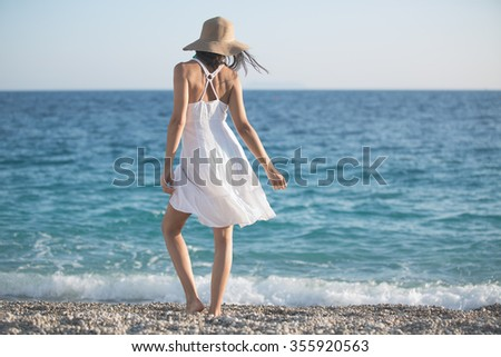 Beautiful woman in a white dress walking on the beach.Relaxed woman breathing fresh air,emotional sensual woman near the sea, enjoying summer.Travel and vacation. Freedom and inspiration concept - stock photo