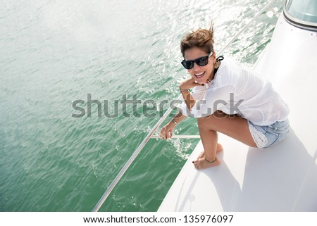 Beautiful woman in a yacht enjoying the summer - stock photo