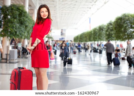 Beautiful woman in airport. Business travel background. - stock photo