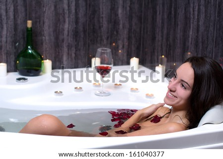 Beautiful woman in bath with rose petals drinking wine - stock photo