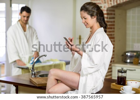 Beautiful woman in bathrobe sitting on kitchen worktop and typing a text message on smartphone while man ironing clothes behind her - stock photo