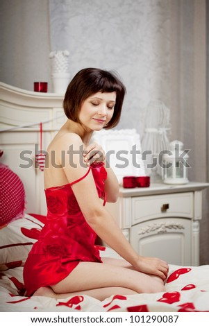 Beautiful woman in bed with hearts - stock photo