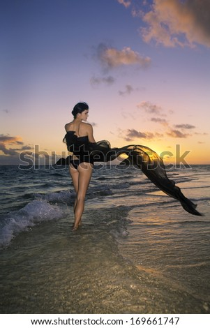 beautiful woman in bikini at the beach at sunrise - stock photo