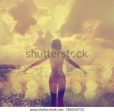 Beautiful Woman in Bikini Standing in the Sea Waves and Enjoying Sunshine with Open Arms - stock photo